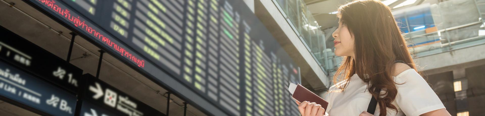 Emotion: Flughafen - Frau- Reisepass - Anzeigetafel