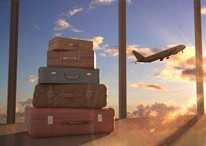 Ein Stapel Koffer im Vordergrund ein startendes Flugzeug im Hintergrund