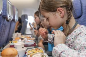 Kind im Flugzeug mit Bordmenü