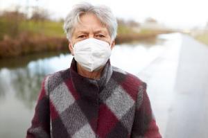 Seniorin mit FFP2-Maske beim Spaziergang